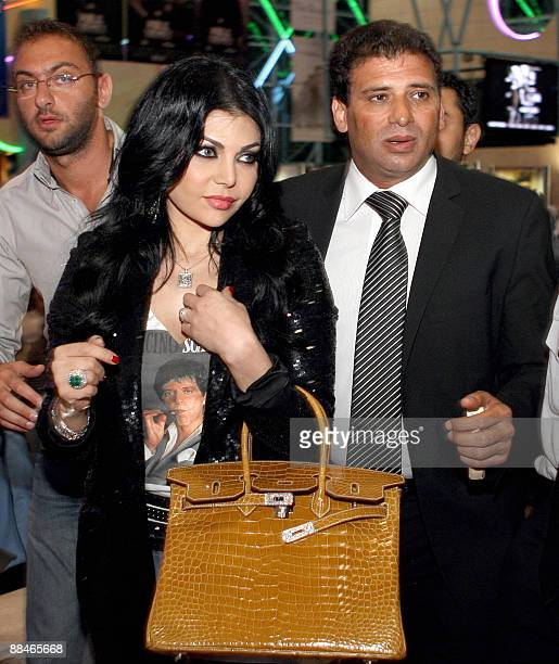 Lebanese model singer and actress Haifa Wehbe arrives with Egyptian film director Khaled Yussef to attend the screening of their new film 'Dokan...