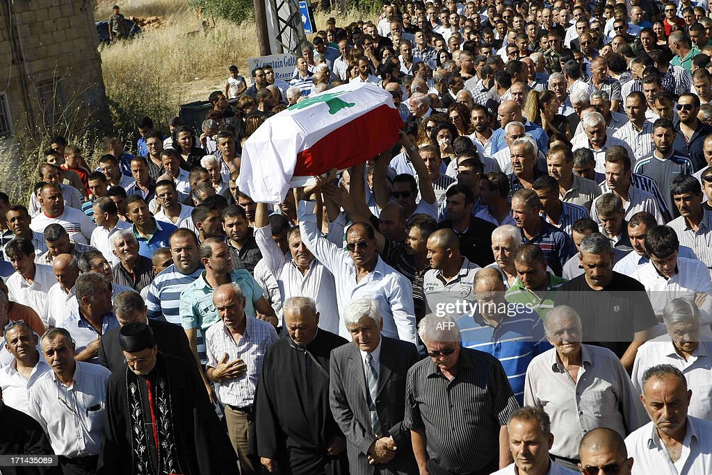 Lebanese mourners carry the coffin of First Lieutenant Samer Tanios, who was killed in clashes with Sunni radicals, during his funeral in the southern town of Rmeish on June 24, 2013. Lebanon's army made significant advances on a complex of buildings used by supporters of radical Sunni cleric Sheikh Ahmad al-Assir in the south, after 16 soldiers died in two days of fighting, military sources said.