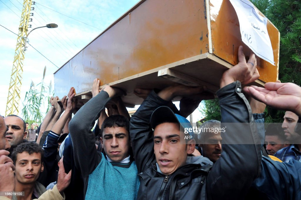 Lebanese mourners carry the coffin of Khodr Mustafa Alameddine, who was among a group of Sunni Muslims killed by the Syrian army after they crossed into Syria to fight alongside rebels, during his funeral in Minieh in northern Lebanon on December 9, 2012. The 22 men died in Tal Kalakh in the central province of Homs late last month after travelling from the northern Lebanese city of Tripoli to join the rebellion against Syrian President Bashar al-Assad, according to a local official and an Islamist leader.