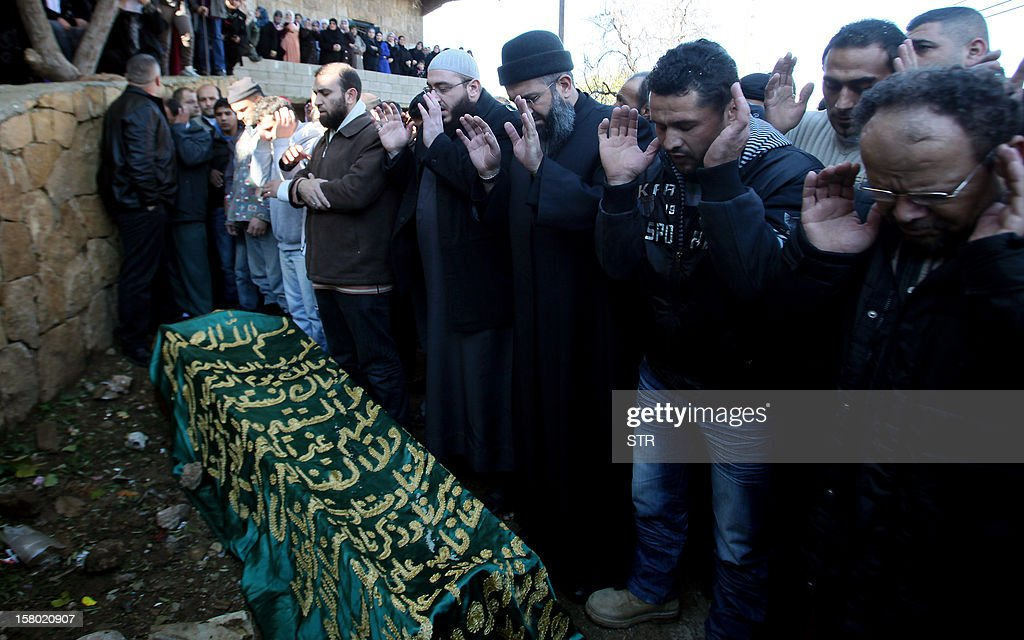 Lebanese mourners pray over the coffin of Abdel Hamid Ali al-Agha, who was among a group of Sunni Muslims killed by the Syrian army after they crossed into Syria to fight alongside rebels, during his funeral in Denniyeh in northern Lebanon on December 9, 2012. The 22 men died in Tal Kalakh in the central Syrian province of Homs late last month after travelling from the northern Lebanese city of Tripoli to join the rebellion against Syrian President Bashar al-Assad, according to a local official and an Islamist leader.