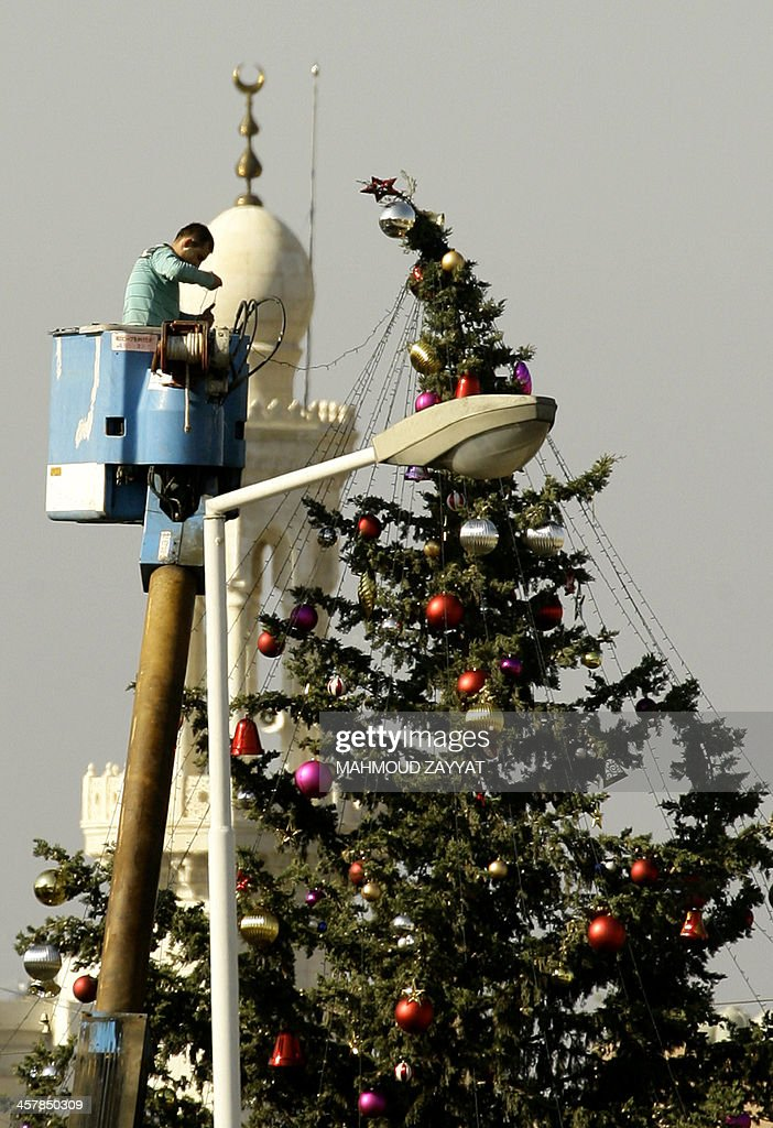 A Lebanese municipality worker decorates a Christmas tree in front of a mosque on December 19, 2013 in Sidon, the majority Sunni Muslim capital of south Lebanon, which is still recovering from a suicide attack on an army checkpoint in which an officer was killed on December 15, as were two armed men who accompanied the attacker, both gunned down by troops manning the checkpoint.