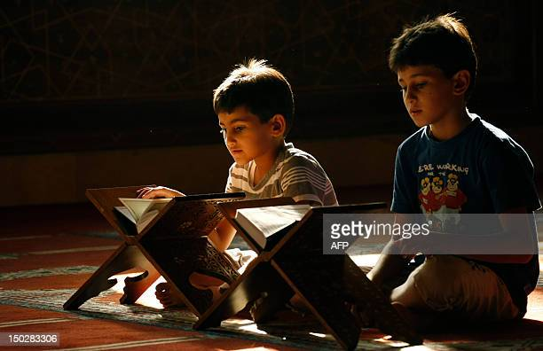 Lebanese Muslim boys read from the Koran Islam's holy book during the holy fasting month of Ramadan at a mosque in the southern Lebanese city of...