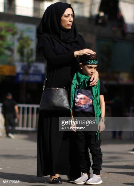 A Lebanese Muslim Shiite woman and her son wearing a Tshirt bearing a picture of Hezbollah secretary general Hassan Nasrallah watch a parade marking...