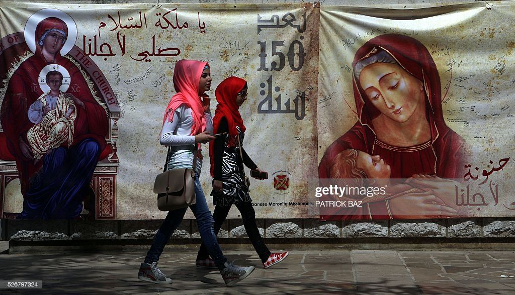 Lebanese Muslim Shiite women walk past a banner depicting Virgin Mary as they pay a visit to the shrine of Our Lady of Lebanon in the town of Harissa north east of the Lebanese capital Beirut, marking the start of the Holy Month of Virgin Mary, on May 1, 2016. Virgin Mary is considered one of the most righteous and greatest women in Islam and is venerated by both Islam and Christianity. / AFP / PATRICK BAZ
