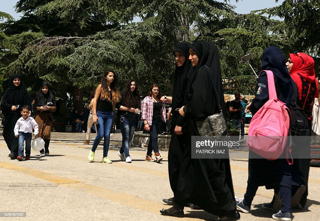 Lebanese Muslim Shiite women walk past Maronite Christian women (C) as they pay a visit to the shrine of Our Lady of Lebanon in the town of Harissa north east of the Lebanese capital Beirut, marking the start of the Holy Month of Virgin Mary, on May 1, 2016. Virgin Mary is considered one of the most righteous and greatest women in Islam and is venerated by both Islam and Christianity. / AFP / PATRICK BAZ