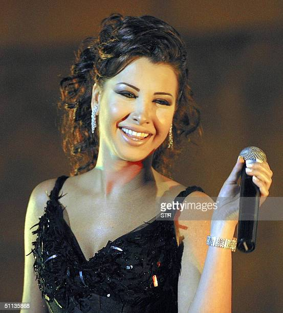 Lebanese new singing star Nancy Ajram performs on stage 01 August 2004 during her concert at the Roman Theater in Carthage as part of her Tunisian...
