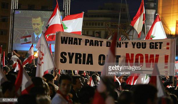 Lebanese opposition protesters wave their national flags and banners calling for the Syrian withdrawal from Lebanon as they watch live on a giant...
