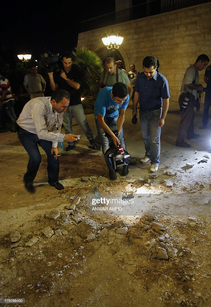 Lebanese people and journalists inspect the damage at a private residence where one of two rockets fired from an unknown location exploded in the early hours of August 2, 2013, just metres from an entrance to the presidential palace in Baabda, around eight kilometres southeast of the Lebanese capital Beirut. The official news agency ANI said the second rocket fell near a Lebanese army training camp in the region of Baabda, causing no casualties as tensions mounted in the east Mediterranean country over the conflict in neighbouring Syria.