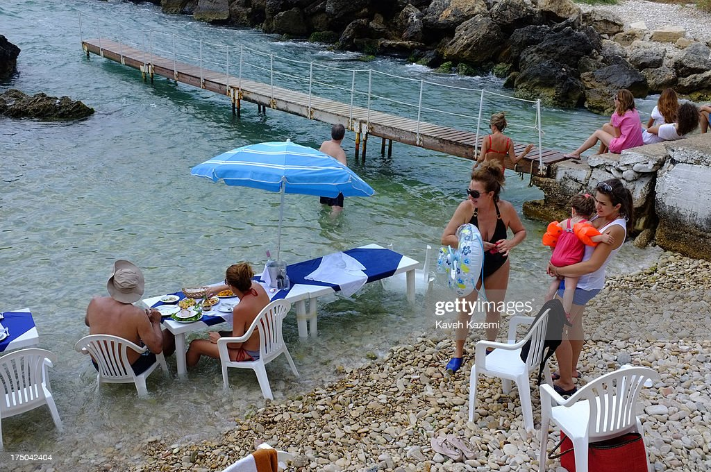 Lebanese people enjoy a day eating and drinking at the beach in Jammal sea food restaurant on July 18, 2013 in Batroun, Lebanon. Despite the rising tensions between different Muslim factions in the country people enjoy their leisure time and continue their daily life as normal.