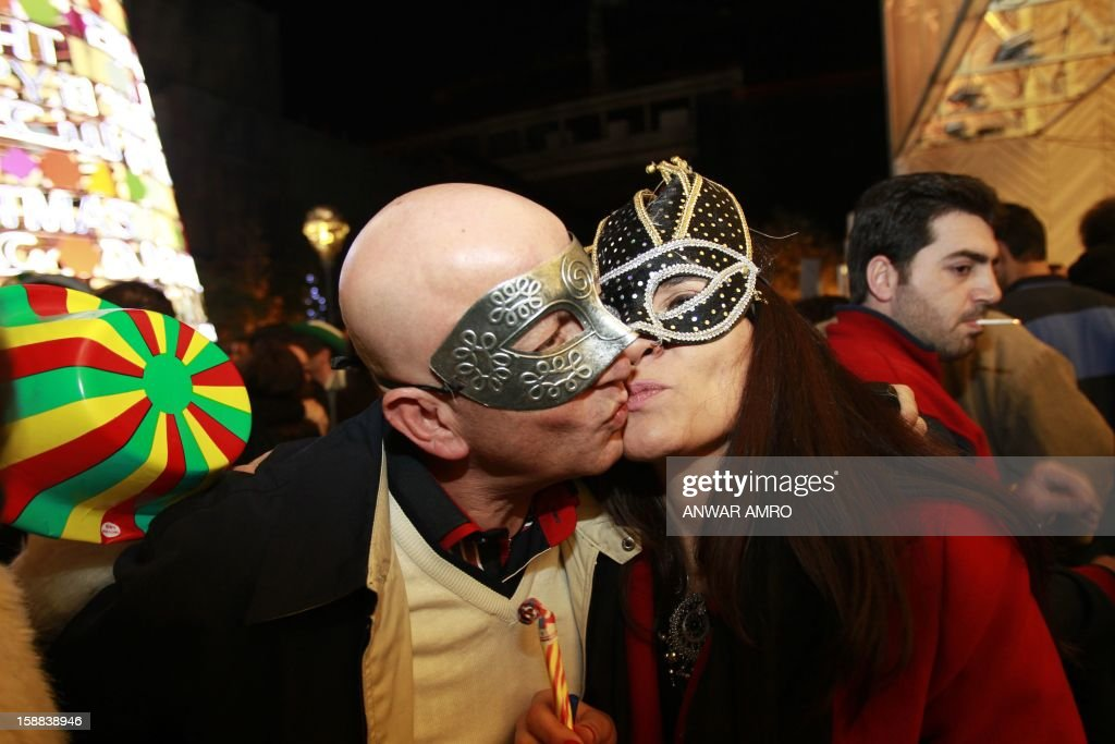 Lebanese people kiss as they celebrate on new year's eve in Beirut, early on January 1, 2013.