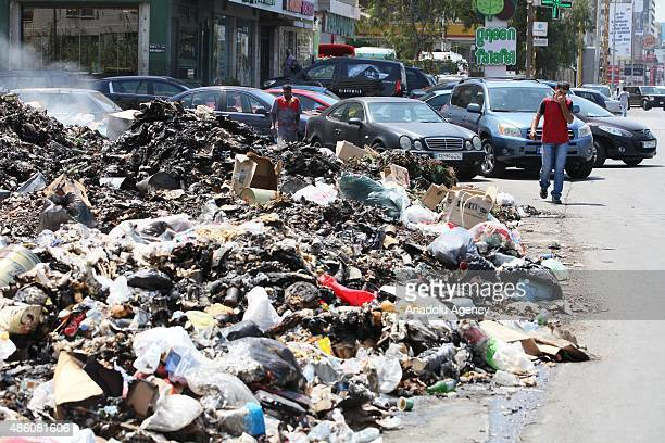 Lebanese people pass by a garbage dump in Beirut Lebanon on August 31 2015 After closing one of the main landfill sites and being stopped the working...