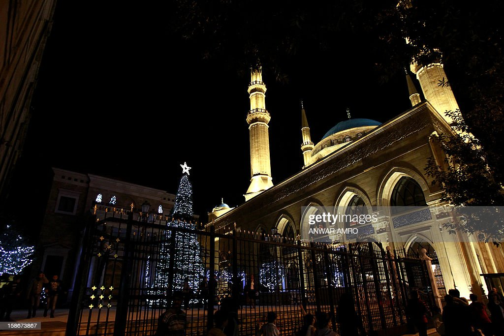 Lebanese people walk past a Christmas tree decorated outside Saint George church next to the Mohammed al-Amin mosque in downtown Beirut on December 23, 2012. AFP PHOTO/ANWAR AMRO