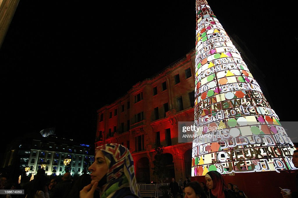 Lebanese people walk past a Christmas tree in Beirut on December 23, 2012.