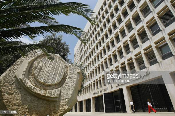 Lebanese people walk past Lebanon's Central Bank building in Beirut on July 21 2009 Lebanon's new government has yet to see the light but its...