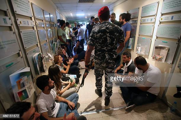 Lebanese policemen walk past activists sitting in a hallway during a surprise sitin at Lebanon's environment ministry to demand the minister's...