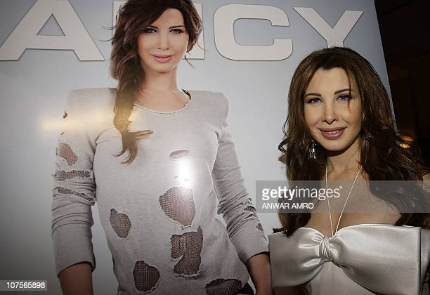 Lebanese pop singer Nancy Ajram poses for pictures in front of her poster during the official launching ceremony of her latest album 'Nancy 7' in...
