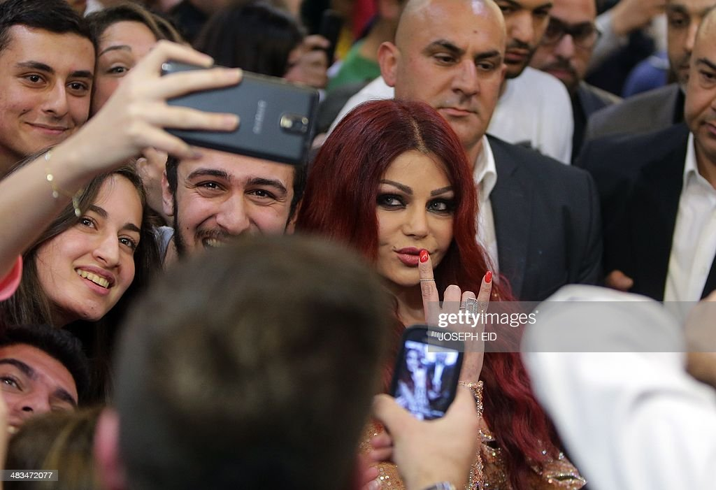 Lebanese pop star Haifa Wehbe poses for pictures with her fans as she arrives for the Premiere of he movie 'Halawet Rooh' at a movie theatre in the town of Dbayeh, North of Beirut on April 8 , 2014.