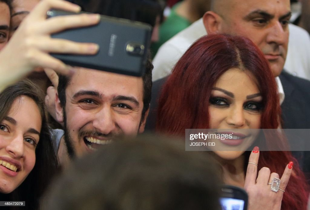 Lebanese pop star Haifa Wehbe (R) poses for pictures with her fans as she arrives for the Premiere of he movie 'Halawet Rooh' at a movie theatre in the town of Dbayeh, North of Beirut on April 8 , 2014.