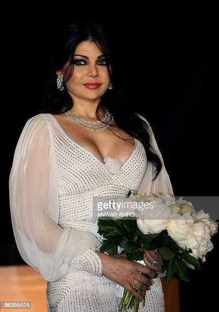 Lebanese pop star Haifa Wehbe poses with a bouquet during a ceremony to celebrate the signing of a new deal with the Middle East's leading record...