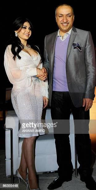 Lebanese pop star Haifa Wehbe shakes hands with Salem alHindi president of Rotana record label during a ceremony to celebrate the signing of a new...