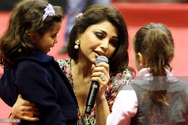 Lebanese pop star Haifa Wehbe sings with children during an event celebrating mother's day in Beirut on March 21 2011 AFP PHOTO/STR