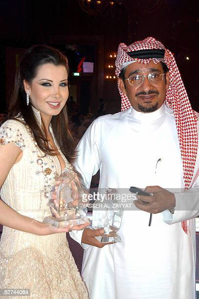 Lebanese pop star Nancy Ajram and Saudi comedian Abdullah alSadhan pose with their trophies after being chosen by Newsweek's Arabic edition as one of...