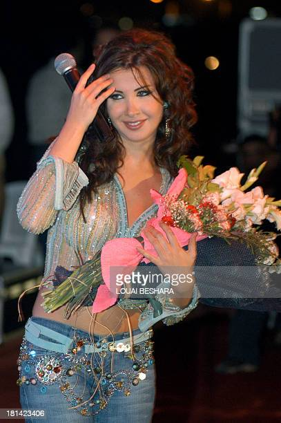 Lebanese pop star Nancy Ajram receives a bouquet of flowers during her performance late 02 September 2004 at a local beach ball tournament in the...