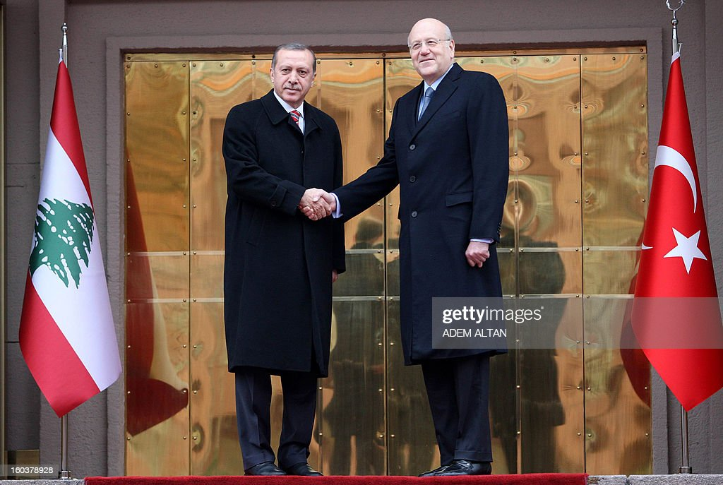 Lebanese Prime Minister Najib Mikati (R) poses with Turkish Prime Minister Recep Tayyip Erdogan (C) as they review an honour guard during a welcoming ceremony in Ankara on January 30,2013. AFP PHOTO/ADEM ALTAN