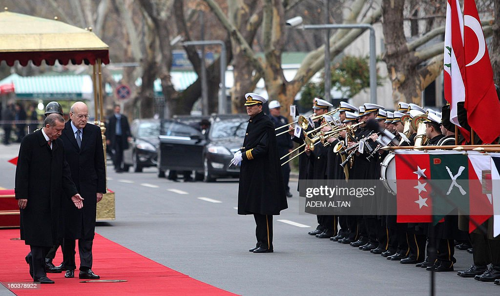 Lebanese Prime Minister Najib Mikati (R) walks with Turkish Prime Minister Recep Tayyip Erdogan (C) as they review an honour guard during a welcoming ceremony in Ankara on January 30, 2013. AFP PHOTO/ADEM ALTAN