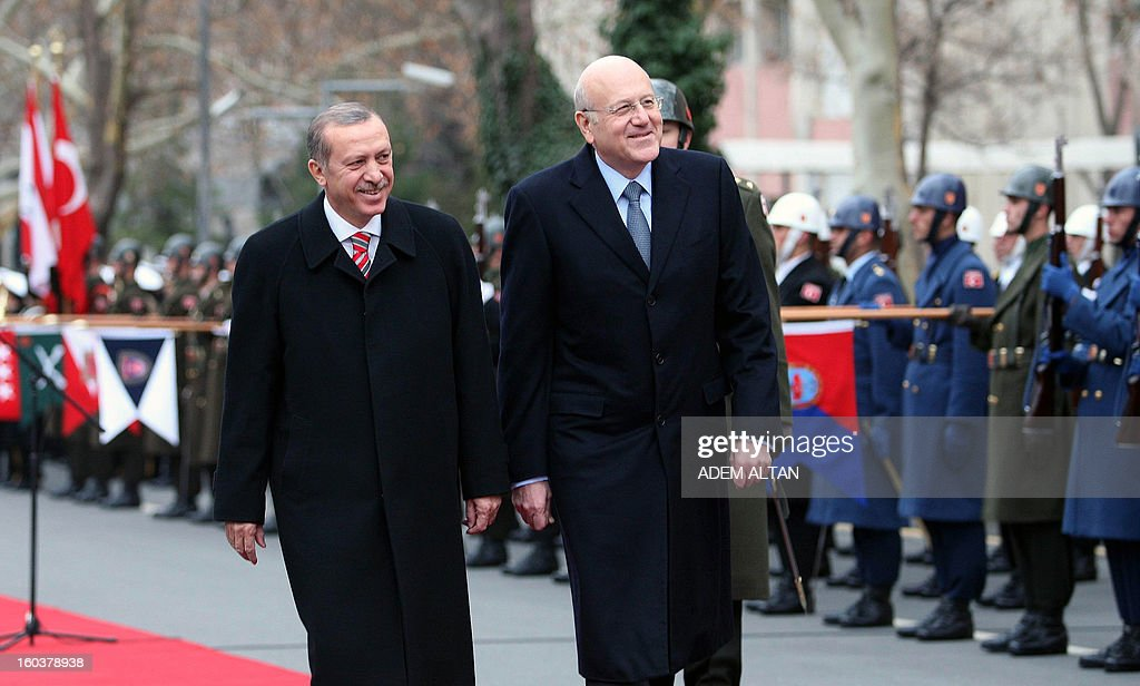 Lebanese Prime Minister Najib Mikati(R) walks with Turkish Prime Minister Recep Tayyip Erdogan as they review an honour guard during a welcoming ceremony in Ankara on January 30, 2013.