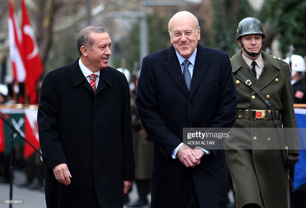 Lebanese Prime Minister Najib Mikati(R) walks with Turkish Prime Minister Recep Tayyip Erdogan (C) as they review an honour guard during a welcoming ceremony in Ankara on January 30, 2013.