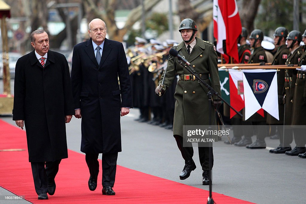 Lebanese Prime Minister Najib Mikati(C) walks with Turkish Prime Minister Recep Tayyip Erdogan as they review an honour guard during a welcoming ceremony in Ankara on January 30, 2013.