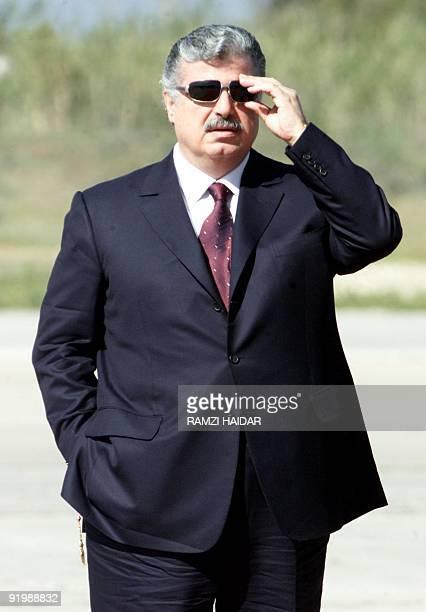 Lebanese Prime Minister Rafiq Hariri adjusts his sunglasses as he awaits the arrival of Syrian President Bashar alAssad at Beirut airport 03 March...