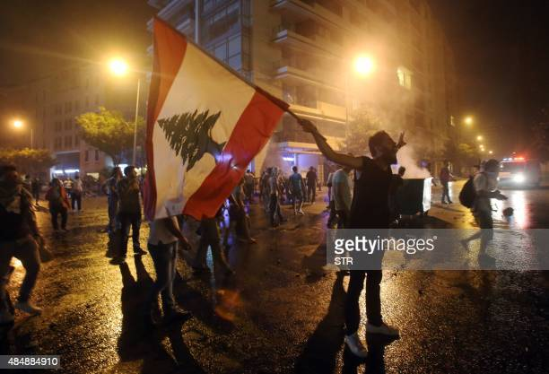 A Lebanese protester holds his national flag and shouts slogans during clashes following a demonstration organised by the 'You Stink' campaign...