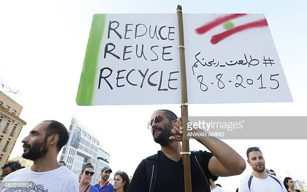 A Lebanese protester holds up a placard during a demonstration in downtown Beirut on August 8 against the recent trash crisis that has seen streets...