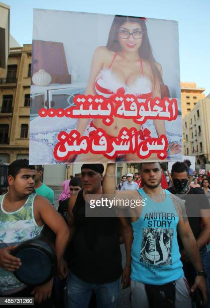 A Lebanese protester raises a poster bearing an image of Lebanese origin Porn Star Mia Khalifa and reading 'It is true that this woman does sex but...