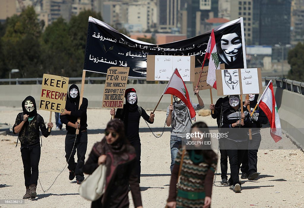 Lebanese protester wearing a Guy Fawkes mask used by the Anonymous movement carry placards during a protest organized by the public sector employees on March 21, 2013 near the Presidential Palace in Baabda east of the Lebanese capital Beirut, to demand an increase in wages.