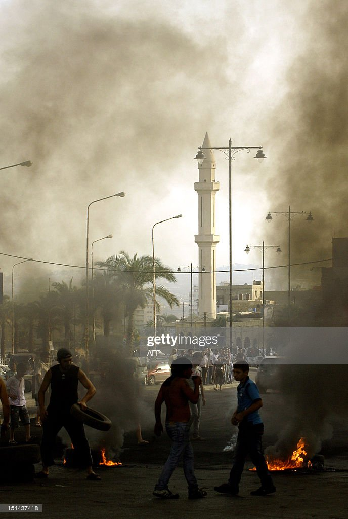 Lebanese protesters burn tyres to block a road in the southern city of Sidon on October 20, 2012 during a protest against a bomb blast in the capital Beirut the day before. Protesters cut off roads in several areas of Lebanon following the assassination of a high profile security official, AFP journalists said. AFP PHOTO/MAHMOUD ZAYYAT