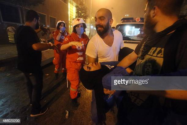 Lebanese protesters carry an injured girl during clashes with riot police following a demonstration organized by 'You Stink' campaign to protest...