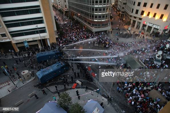 Lebanese protesters chant slogans as riot police fire water cannons following a demonstration organized by 'You Stink' campaign to protest against...