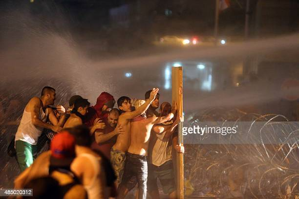 Lebanese protesters hide from water cannons behind a wooden plank during clashes with riot police following a demonstration organized by 'You Stink'...