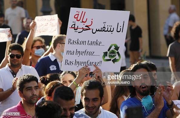 Lebanese protesters hold a placard reading in Arabic 'I breathe garbage' during a demonstration against the ongoing trash crisis on July 25 in the...