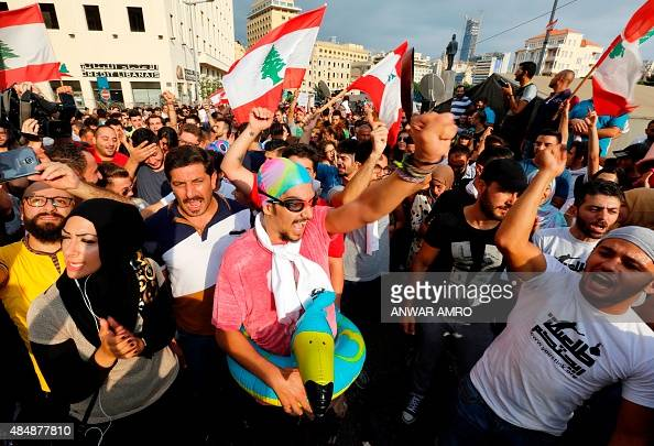 Lebanese protesters hold their national flags and shout slogans during a demonstration organised by the 'You Stink' campaign against the ongoing...
