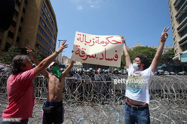 Lebanese protesters raise a placard reading 'government of garbage corruption and thefts' in front of riot policemen during a demonstration to...