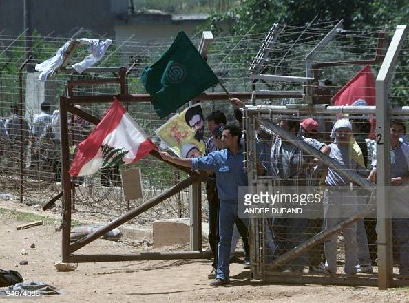 Lebanese protesters wave Amal Hezbollah and Lebanese flags near the barbed wire border with Israel in Kfar Kila 28 May 2000 Lebanese civilians opened...