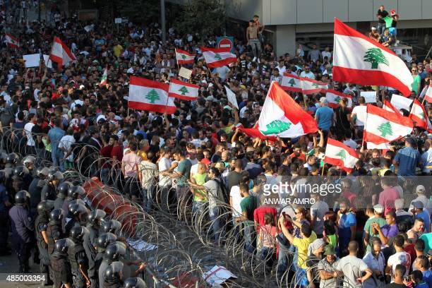 Lebanese protesters wave the national flag in front of a barbed wire fence during a demonstration organized by 'You Stink' campaign to protest...