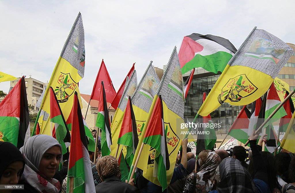 Lebanese protestor waves the Hezbollah flag and the Palestinian flag during a protest against the ongoing attack on Gaza outside the offices of the United Nations Economic and Social Commission for Western Asia (ESCWA) in Lebanese capital Beirut, on November 17, 2012. Lebanese political factions alongside their Palestinian counterparts gathered in the Lebanese capital, as the ongoing assault on Gaza strip took the death toll from three days of Israeli raids to 40, medics said.