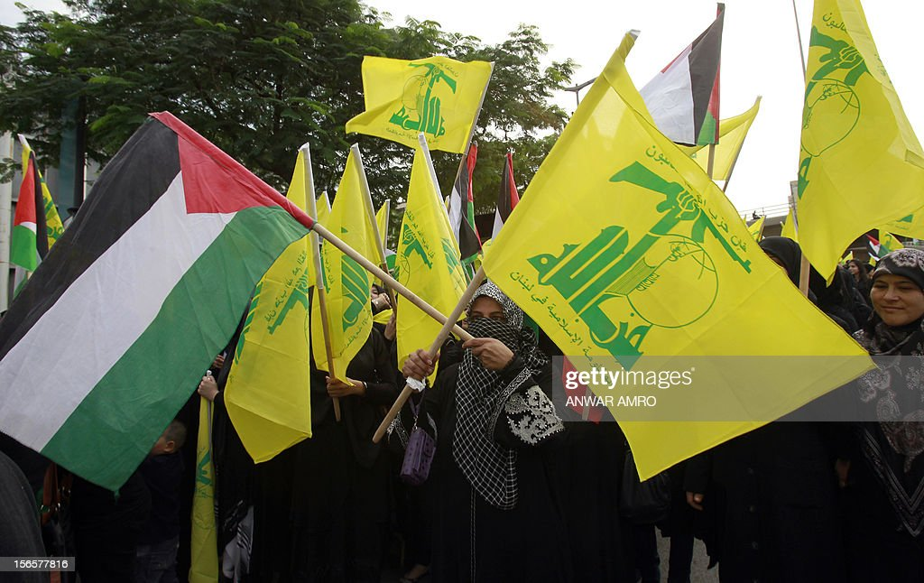 A Lebanese protestor waves the Hezbollah flag and the Palestinian flag during a protest against the ongoing attack on Gaza outside the offices of the United Nations Economic and Social Commission for Western Asia (ESCWA) in Lebanese capital Beirut, on November 17, 2012. Lebanese political factions alongside their Palestinian counterparts gathered in the Lebanese capital, as the ongoing assault on Gaza strip took the death toll from three days of Israeli raids to 40, medics said. AFP PHOTO / ANWAR AMRO