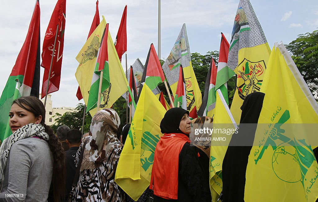Lebanese protestors wave the Hezbollah flag and the Palestinian flag during a protest against the ongoing attack on Gaza outside the offices of the United Nations Economic and Social Commission for Western Asia (ESCWA) in Lebanese capital Beirut, on November 17, 2012. Lebanese political factions alongside their Palestinian counterparts gathered in the Lebanese capital, as the ongoing assault on Gaza strip took the death toll from three days of Israeli raids to 40, medics said. AFP PHOTO / ANWAR AMRO