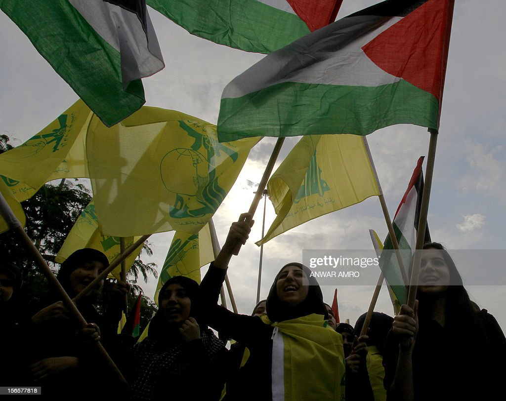 Lebanese protestors wave the Hezbollah flag and the Palestinian flag during a protest against the ongoing attack on Gaza outside the offices of the United Nations Economic and Social Commission for Western Asia (ESCWA) in Lebanese capital Beirut, on November 17, 2012. Lebanese political factions alongside their Palestinian counterparts gathered in the Lebanese capital as the ongoing assault on Gaza strip took the death toll from three days of Israeli raids to 40, medics said. AFP PHOTO / ANWAR AMRO